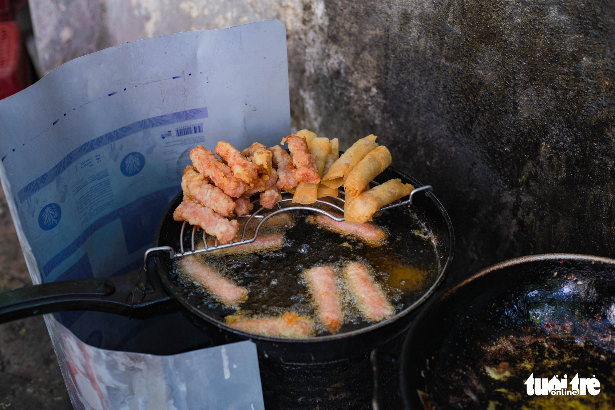 A pan of fried fermented pork roll at the street food stall of Nguyen Thi Thanh, 80, near Thanh Cong Secondary School in Hanoi. Photo: Hong Tham / Tuoi Tre