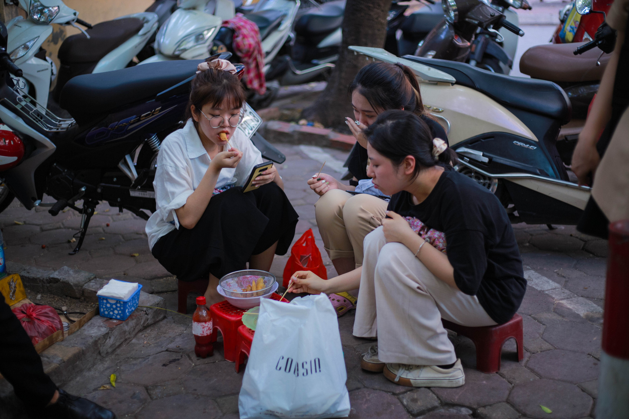 A group of friends enjoys their food at the street food stall of Nguyen Thi Thanh, 80, near Thanh Cong Secondary School in Hanoi. Photo: Hong Tham / Tuoi Tre