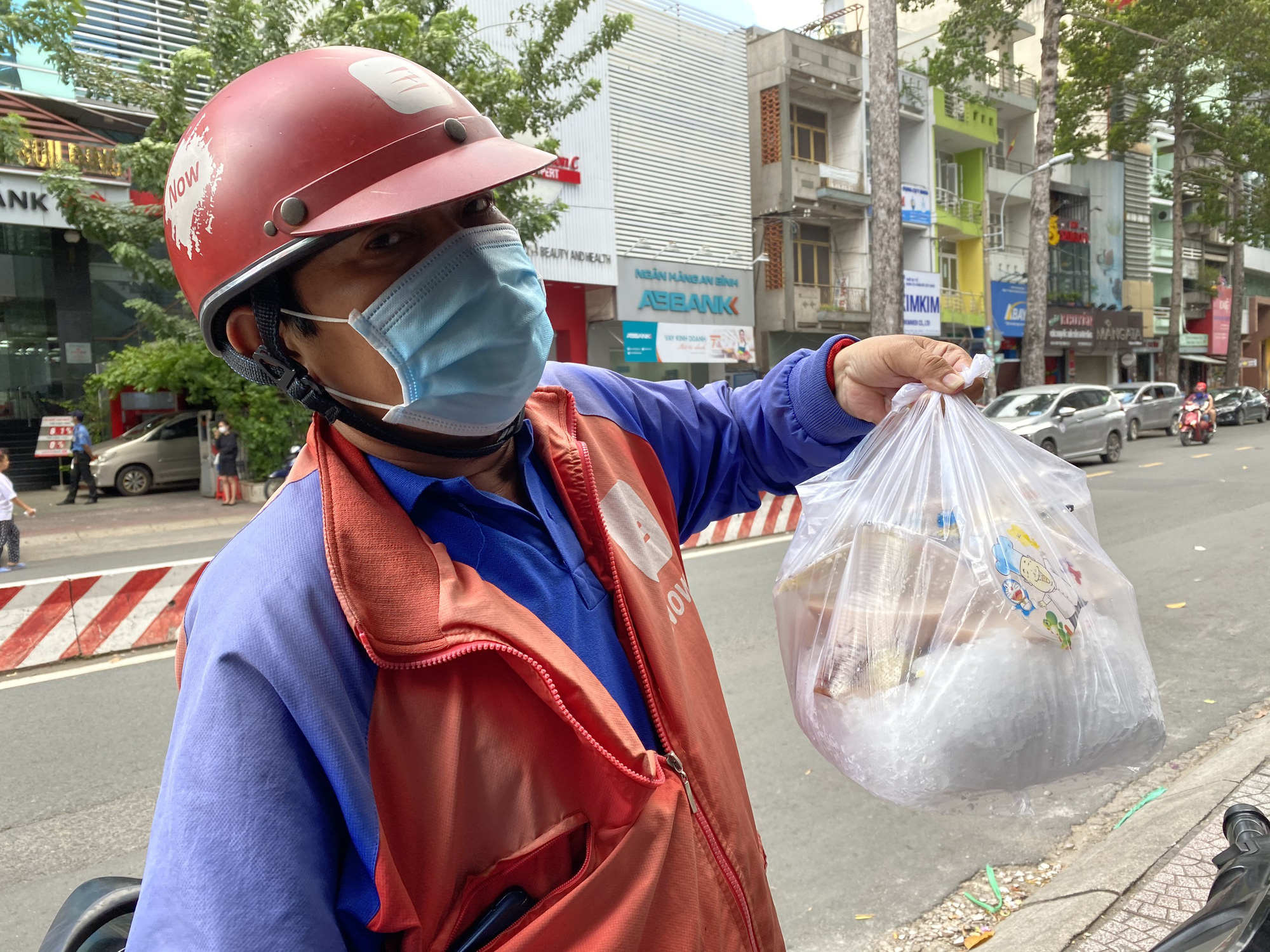 A tech-based delivery men holds a bag of red bean sweet soup servings outside a dessert store in Ho Chi Minh City, Vietnam. Photo: Phan Tran / Tuoi Tre