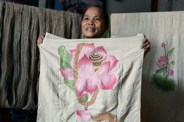 Phan Thi Thuan poses with with a hand-made scarf she made from lotus 'silk' at her workshop in Hanoi. Photo: AFP