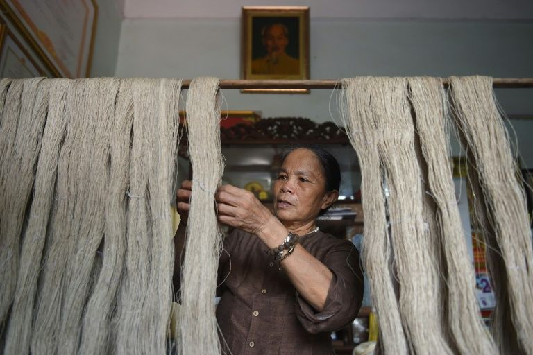 This photograph taken on August 26, 2020 shows Vietnamese weaver, Phan Thi Thuan checking 'lotus silk' yarns at her workshop in Hanoi. Photo: AFP