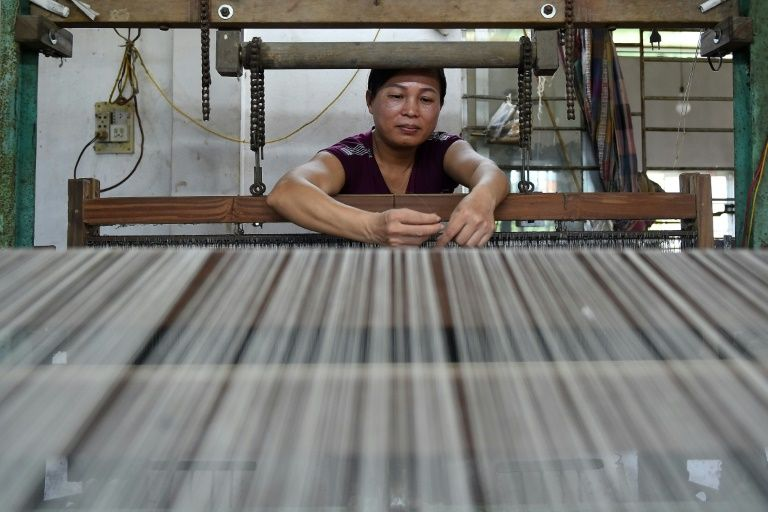 This photograph taken on August 26, 2020 shows a Vietnamese weaver working on 'lotus silk' yarns at a workshop in Hanoi. Photo: AFP