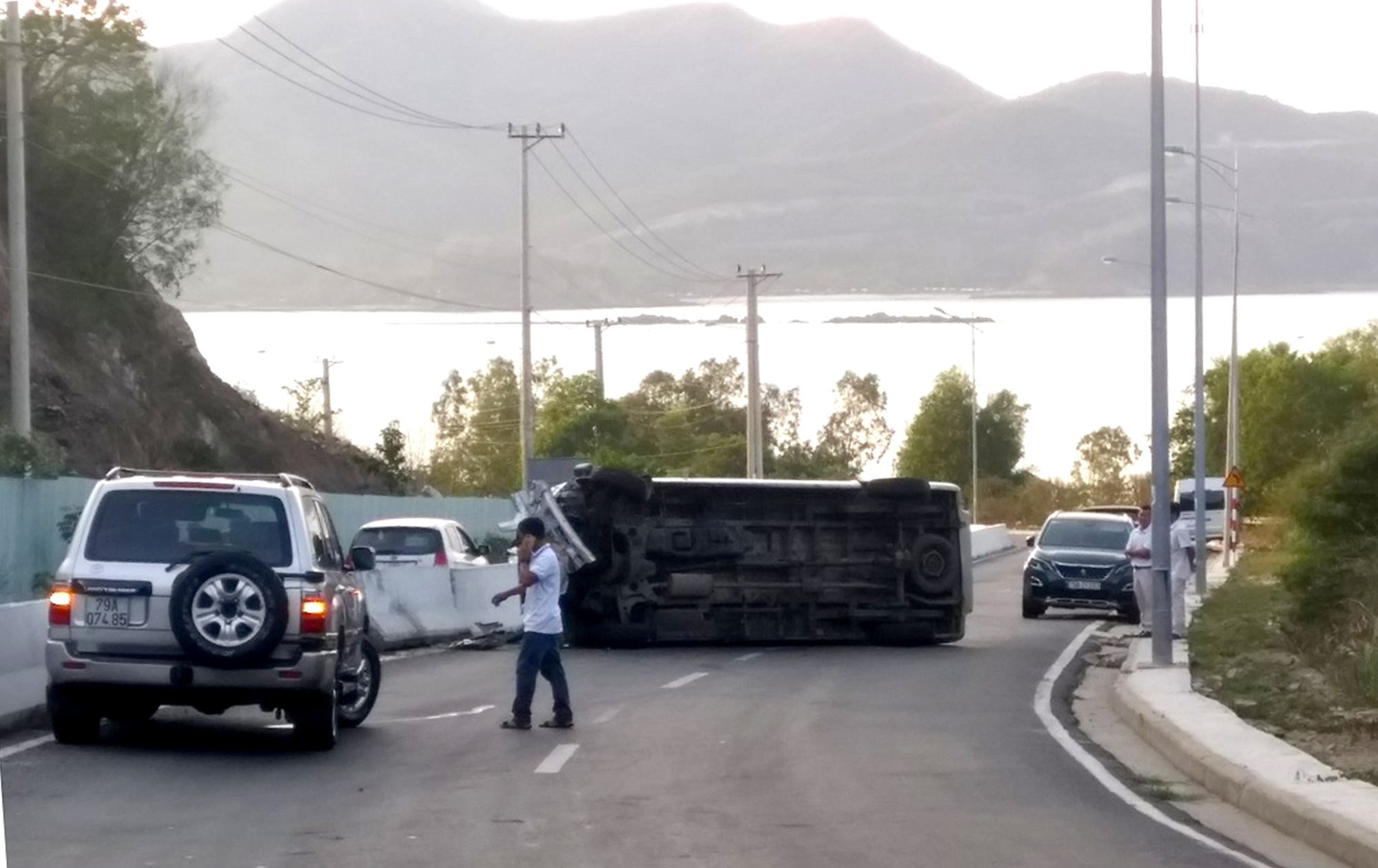 A 16-seat passenger van is on its side after hitting a concrete divider on the Cu Hin mountain pass in Nha Trang City, Khanh Hoa Province, Vietnam, August 30, 2020. Photo: Phan Song Ngan / Tuoi Tre