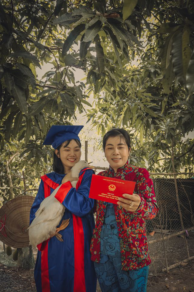 A student in a graduation gown is seen holding a duck, her family's livelihood, while her mother holds a high school diploma. Photo: Pham Van Thong