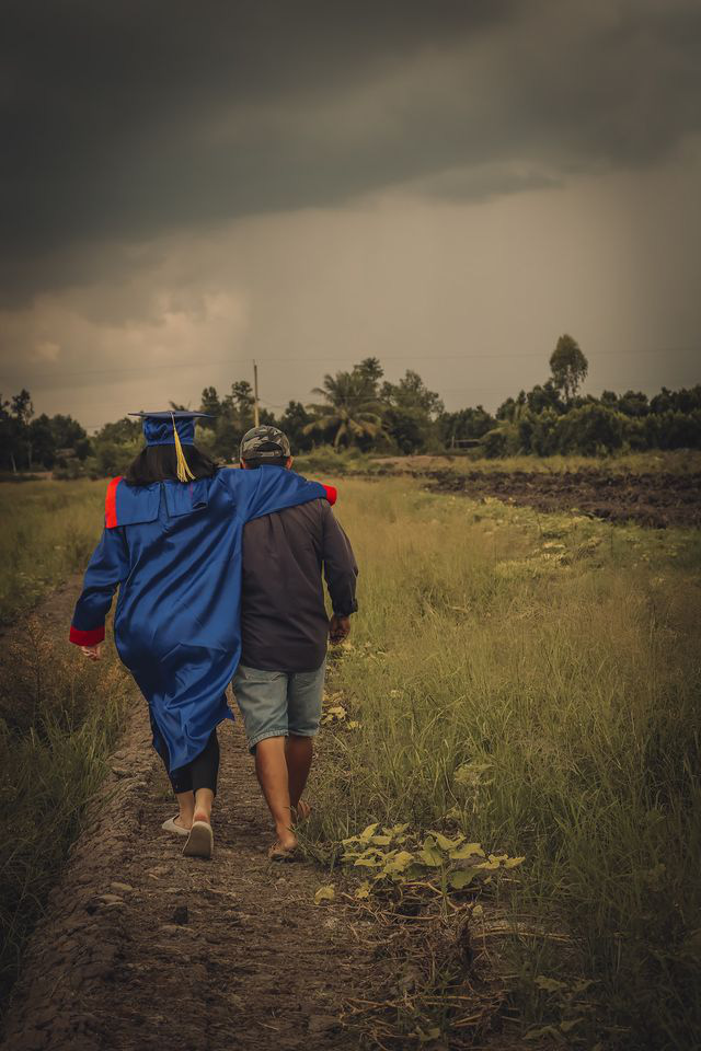 A student in a graduation gown is seen walking next to her father on the rural field. Photo: Pham Van Thong