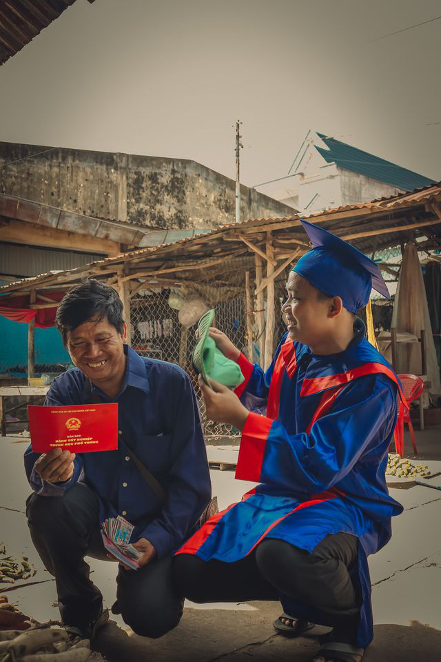 A student in a graduation gown is seen fanning his father while he reads a high school diploma. Photo: Pham Van Thong