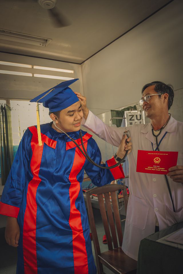 A student in a graduation gown is seen using the stethoscope of his father in a medical clinic. Photo: Pham Van Thong