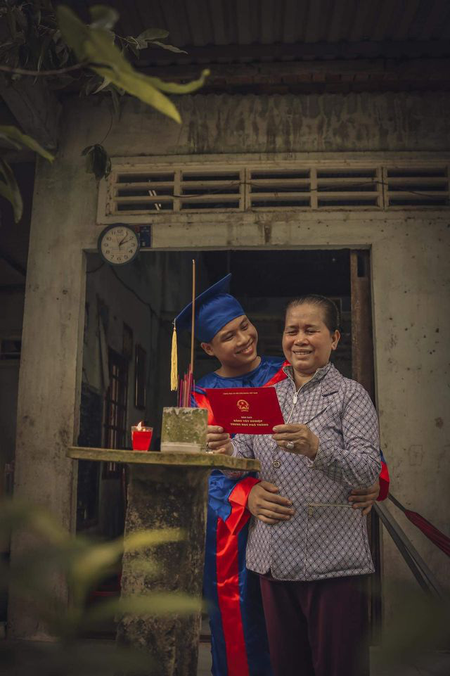 A student in a graduation gown is seen next to his mother in front of the family's altar. Photo: Pham Van Thong