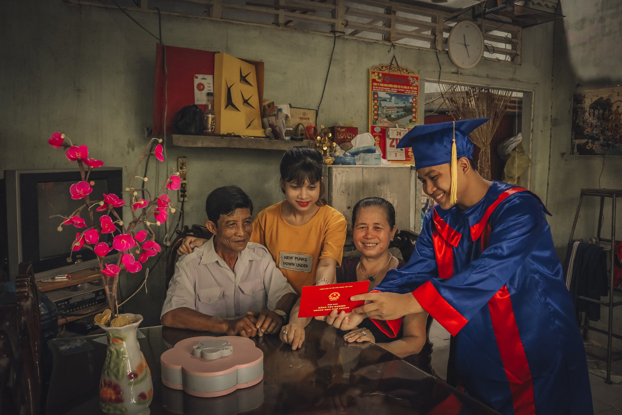 A student in a graduation gown is seen showing a high school diploma to his family. Photo: Pham Van Thong