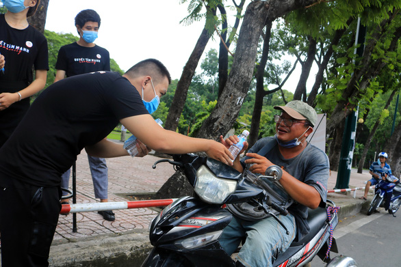 A member of the group 'Quyet tam manh' gives a bottle of water to a lottery ticket seller in Go Vap District, Ho Chi Minh City, September 2, 2020. Photo: Nhat Thinh / Tuoi Tre