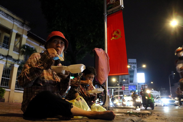Two female scrap dealers eat free meals given by the group 'Quyet tam manh' in Ho Chi Minh City, September 2, 2020. Photo: Hoang An / Tuoi Tre