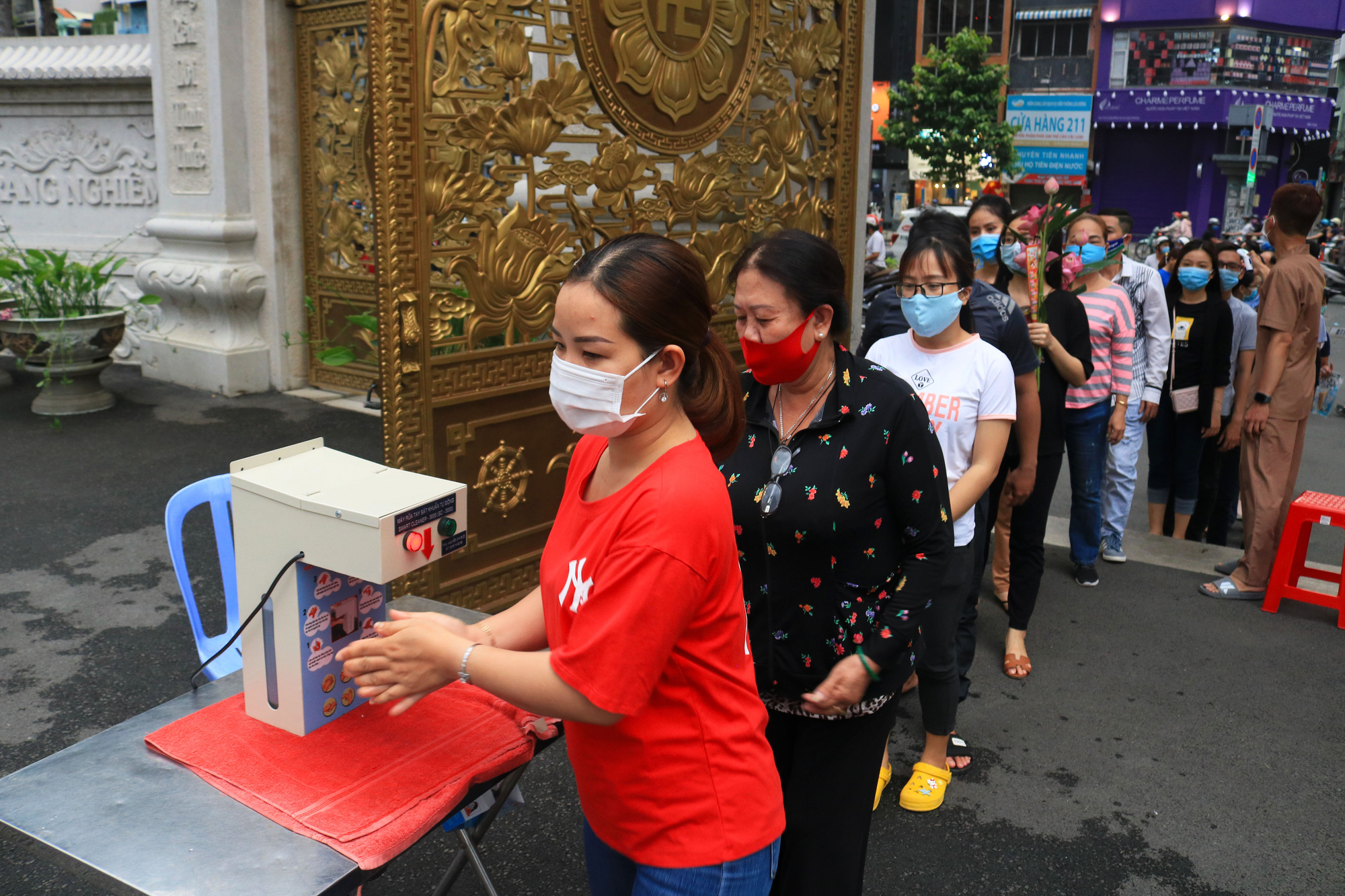 People line up at a hand sanitizer dispenser before entering Viet Nam Quoc Tu Pagoda amid the novel coronavirus disease (COVID-19) outbreak on Vu Lan Festival in Ho Chi Minh City, Vietnam, September 2, 2020. Photo: Nhat Thinh / Tuoi Tre