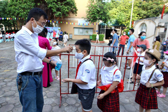 Students queue to have their body temperature checked before attending the school-year opening ceremony at Nguyen Dinh Chieu Elementary School in Hanoi, September 5, 2020. Photo: Nguyen Khanh / Tuoi Tre