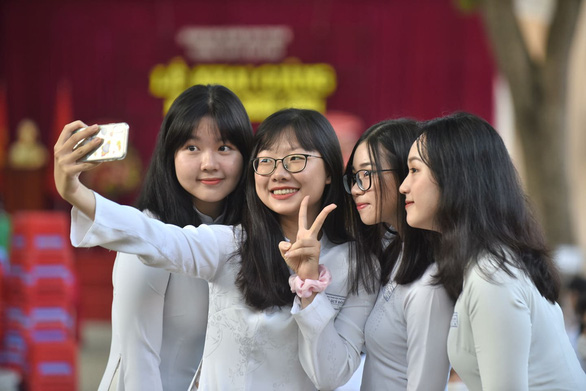 A group of students takes a photo while attending the school-year opening ceremony at Le Quy Don High School in District 3, Ho Chi Minh City, September 5, 2020. Photo: Duyen Phan / Tuoi Tre