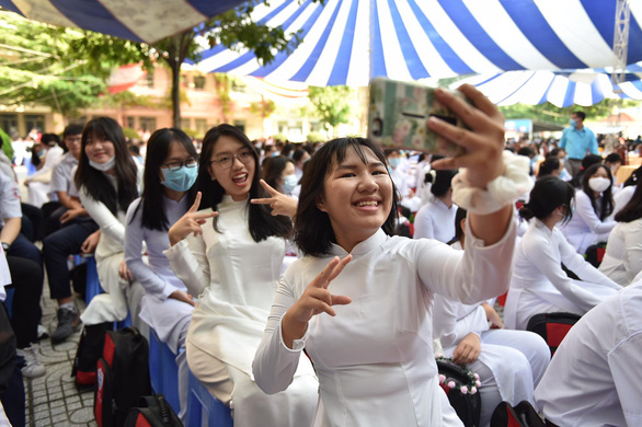 A group of students takes a photo while attending the school-year opening ceremony at Phu Nhuan High School in Phu Nhuan District, Ho Chi Minh City, September 5, 2020. Photo: Ngoc Phuong / Tuoi Tre