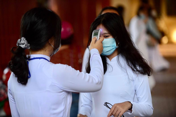 A student has her body temperature checked before attending a school-year opening ceremony at Mac Dinh Chi High School in District 6, Ho Chi Minh City, September 5, 2020. Photo: Quang Dinh / Tuoi Tre