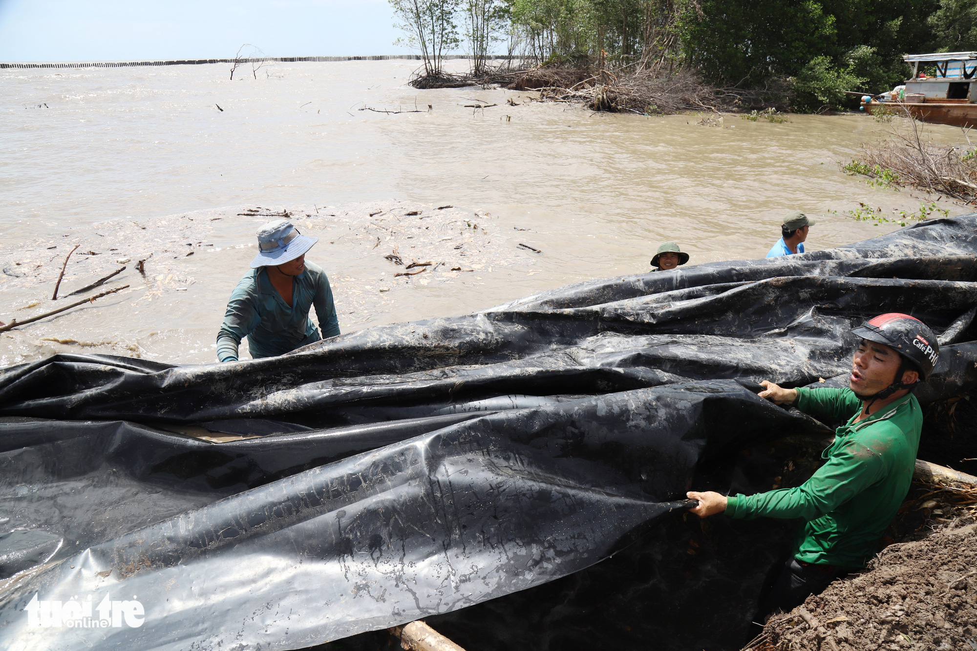 People fortify a section of coastal embankment in Ca Mau Province, Vietnam. Photo: Chi Quoc / Tuoi Tre
