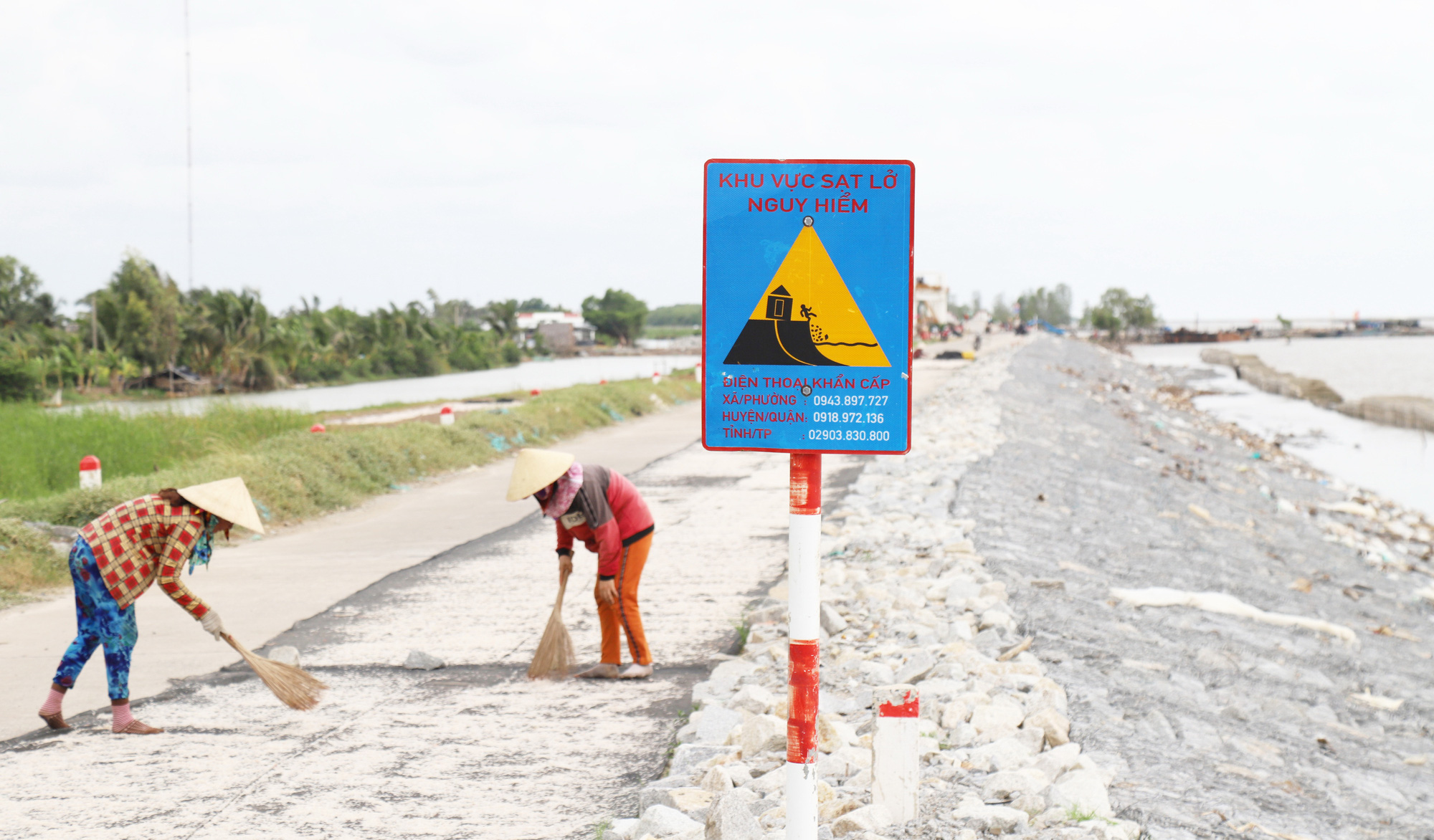 A warning sign is put at an embankment section affected by erosion in Ca Mau Province, Vietnam. Photo: Chi Quoc / Tuoi Tre