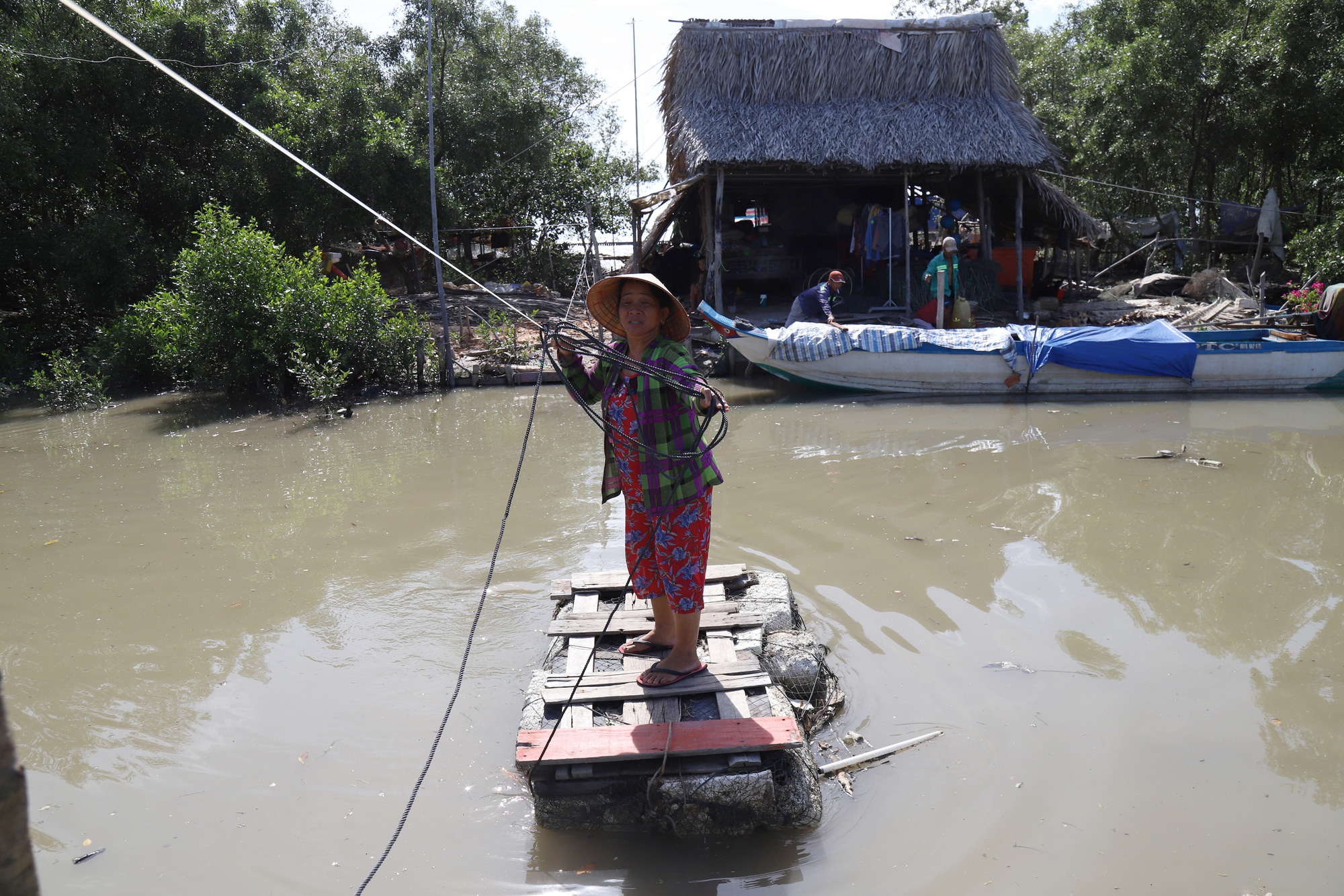 A resident travels on a makeshift raft in an area affected by coastal erosion in Ca Mau Province, Vietnam. Photo: Chi Quoc / Tuoi Tre