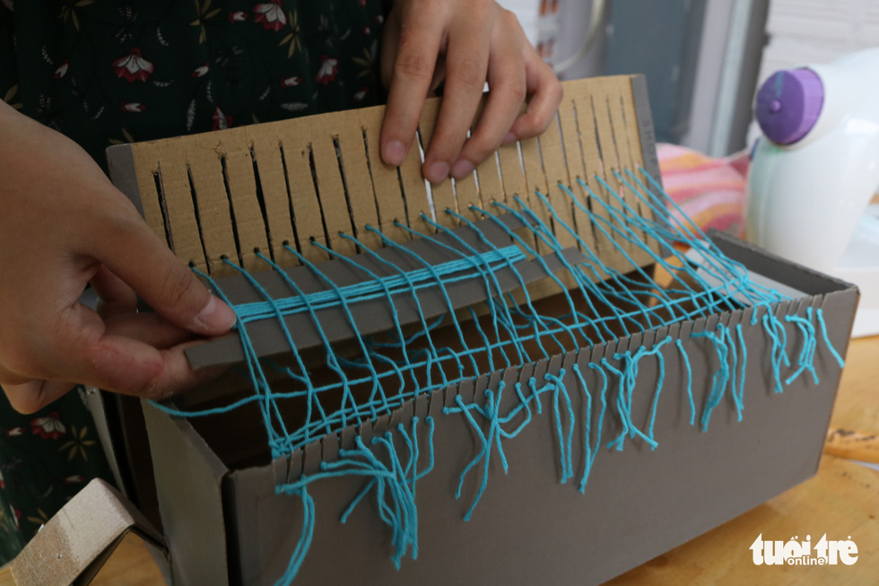 Pham Thi Kim Hang weaves recycled fibers in to a piece of cloth using a homemade loom. Photo: Hoang An / Tuoi Tre