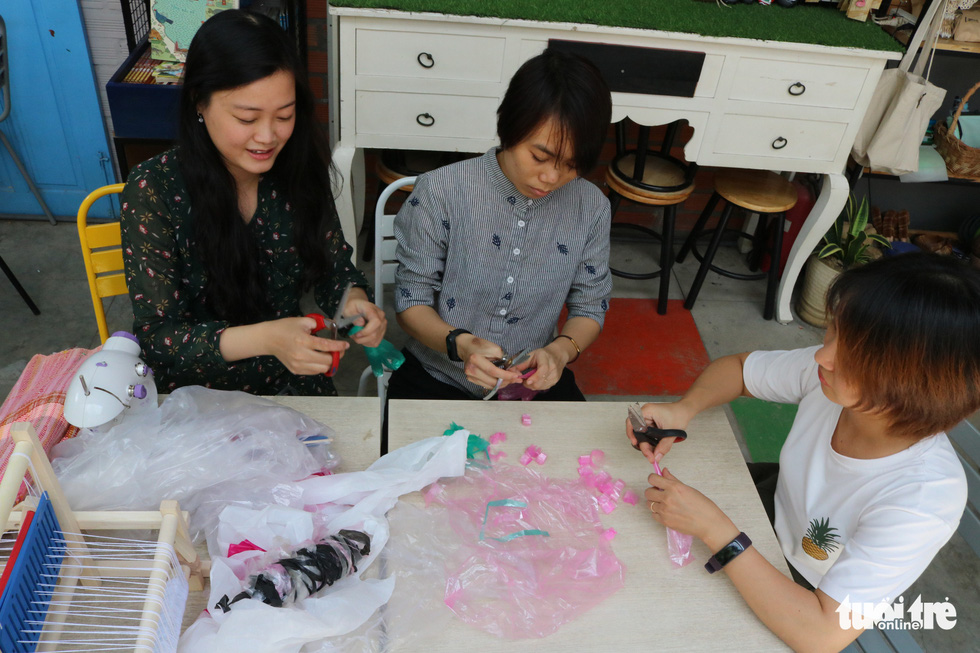Pham Thi Kim Hang (left) and her friends process recycled plastic for making bags. Photo: Hoang An / Tuoi Tre