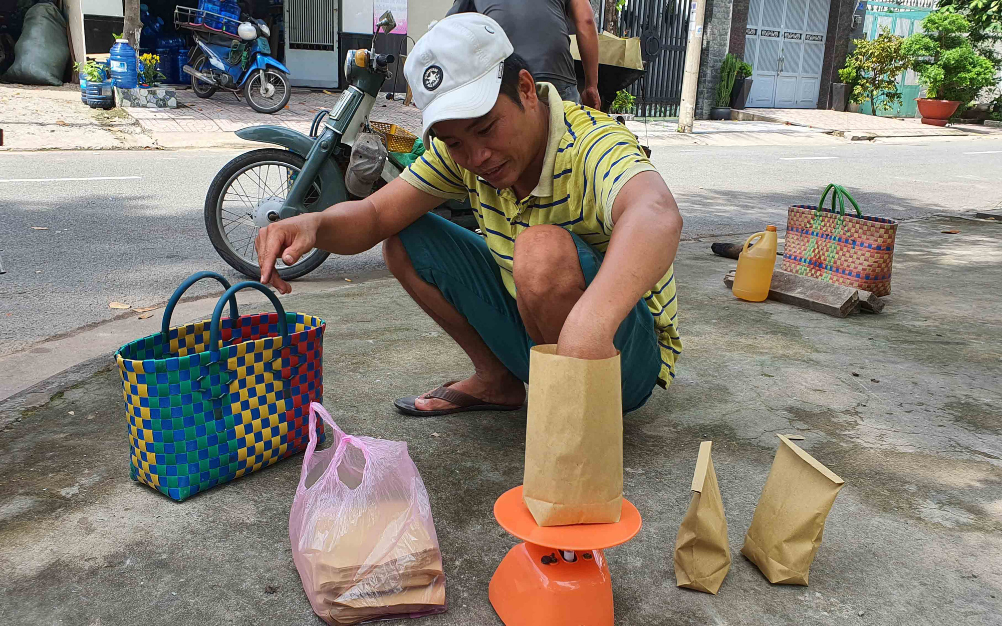 Ngo Dinh Phong, Loi's nephew, portions roasted hazelnuts into paper bags at their roadside stall in Ho Chi Minh City, Vietnam. Photo: Manh Dung / Tuoi Tre