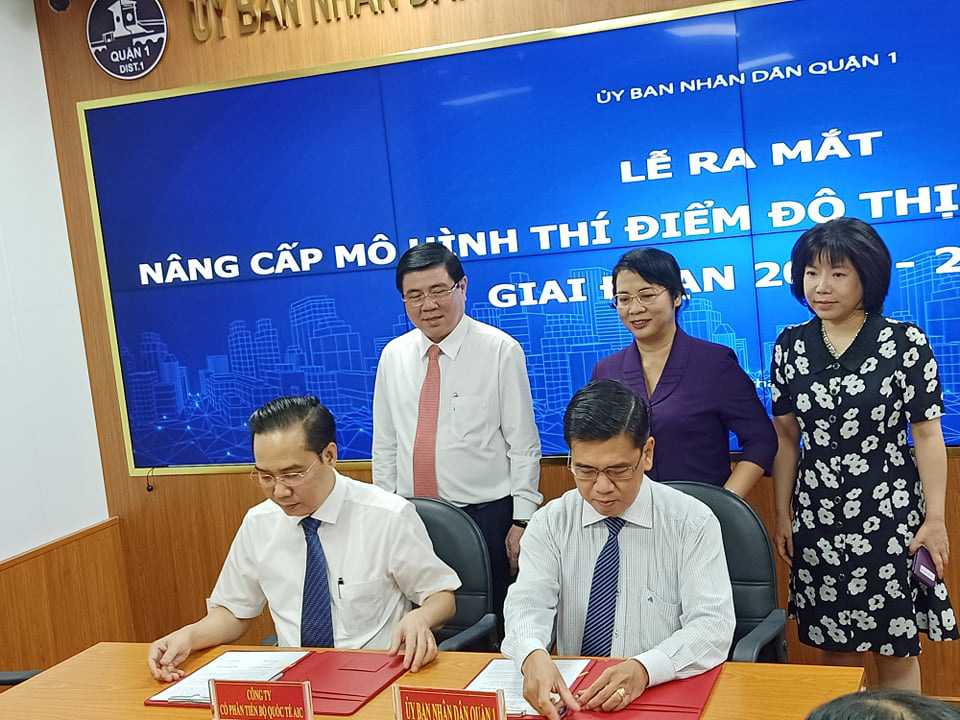 Ho Chi Minh City chairman Nguyen Thanh Phong (standing, left) witnesses the signing of a cooperation agreement between the District 1 People's Committee and a unit coordinating the implementation of the pilot smart-city model. Photo: Mai Huong / Tuoi Tre