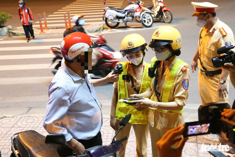 A traffic policewoman measures the breath alcohol concentration of a driver in Ho Chi Minh City, September 9, 2020. Photo: Minh Hoa / Tuoi Tre