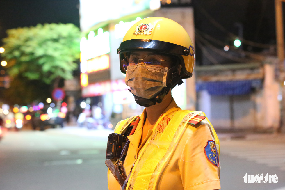 A policewoman of an all-female escort team stands at a checkpoint to handle traffic violation cases in Ho Chi Minh City, September 9, 2020. Photo: Minh Hoa / Tuoi Tre