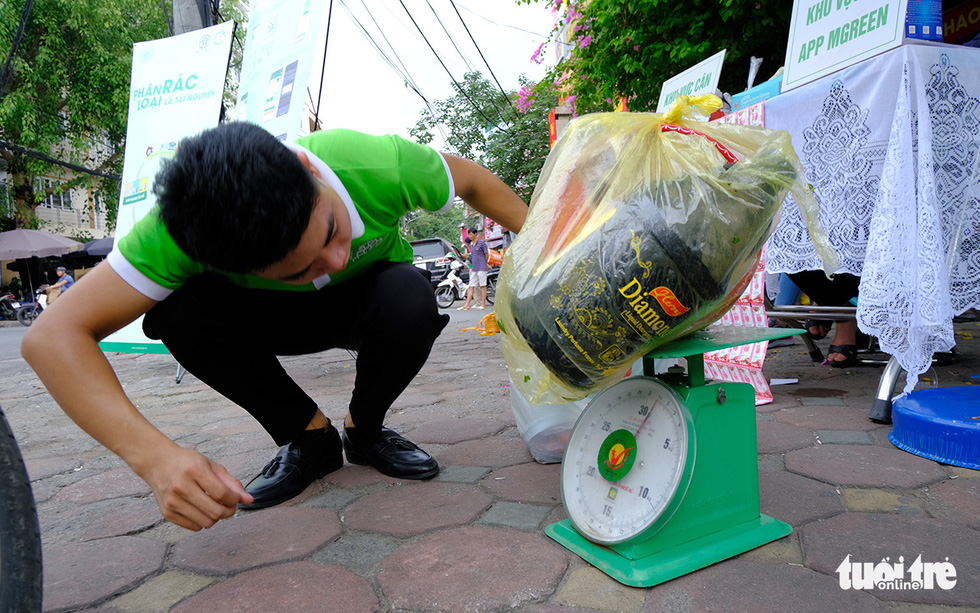 An URENCO worker weighs a bag of sorted trash at an URENCO exchange point in Dong Da District, Hanoi, September 12, 2020. Photo: Ha Thanh / Tuoi Tre