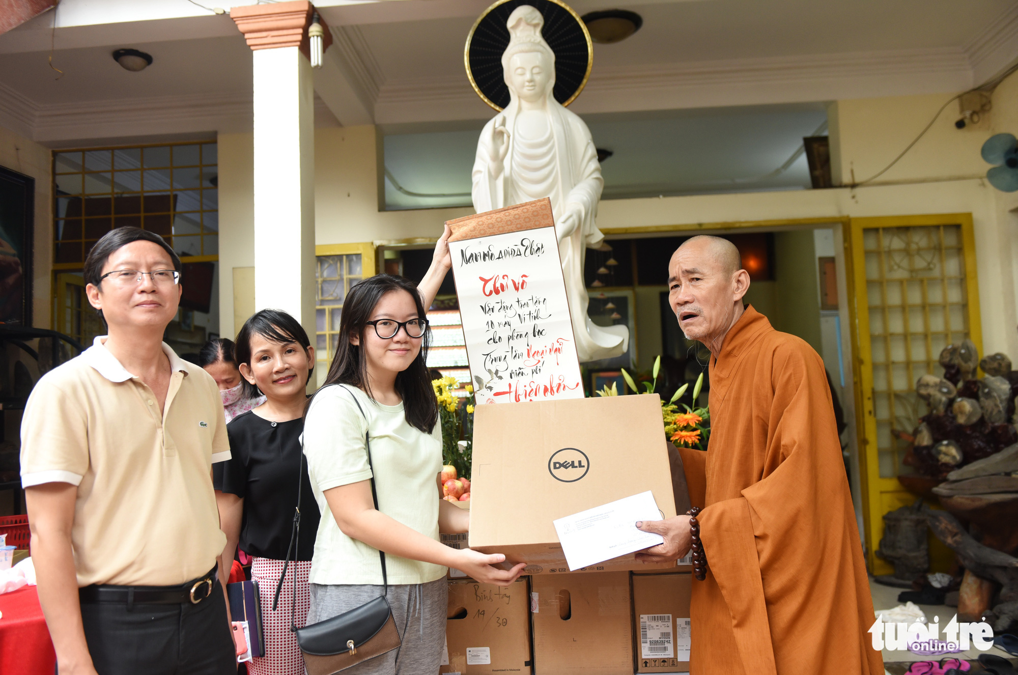 Vo Minh Thu (third left), a volunteer foreign language teacher at La Pagoda in Go Vap District, Ho Chi Minh City, donates personal computers to the pagoda to be used in language teaching, September 13, 2020. Photo: Duyen Phan / Tuoi Tre