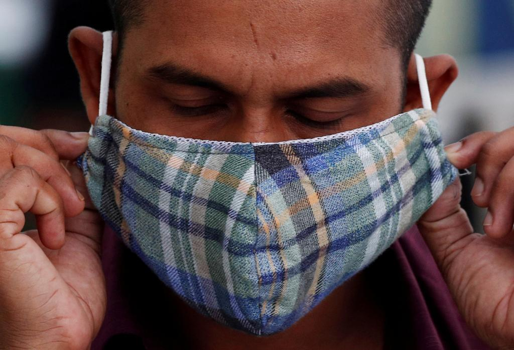 A migrant worker puts on a mask after a nose swab at a dormitory, amid the coronavirus disease (COVID-19) outbreak in Singapore May 15, 2020. Photo: Reuters