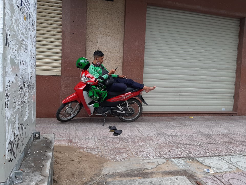 A delivery worker wearing the uniform of multi-service platform Grab is seen relaxing on top of his motorbike while waiting for a new order in Ho Chi Minh City, Vietnam. Photo: M.L. / Tuoi Tre