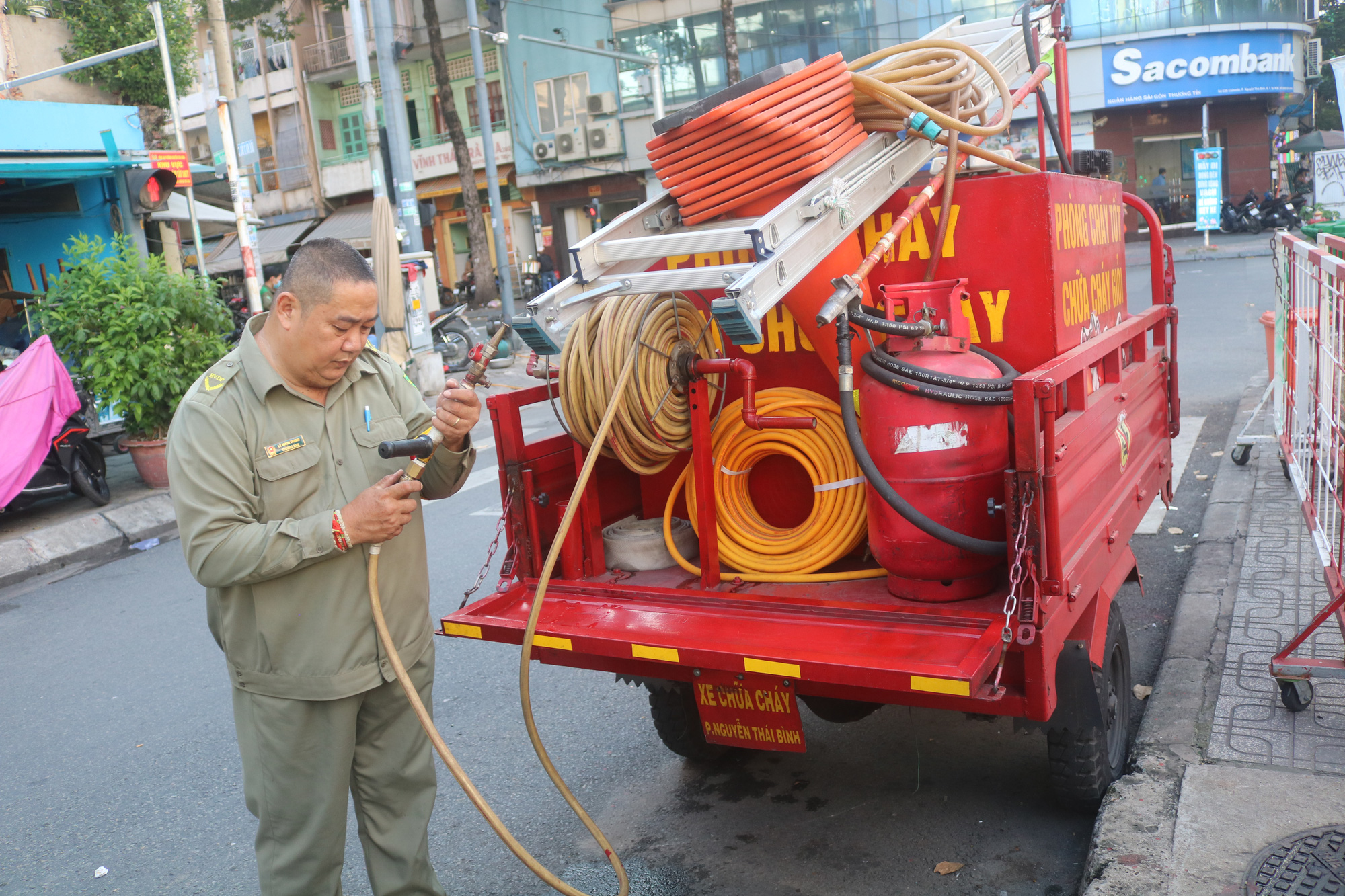 Ly Nhon Thanh inspects the hose of his fire bike modified from a three-wheeled motorbike. Photo: Kim Ut / Tuoi Tre