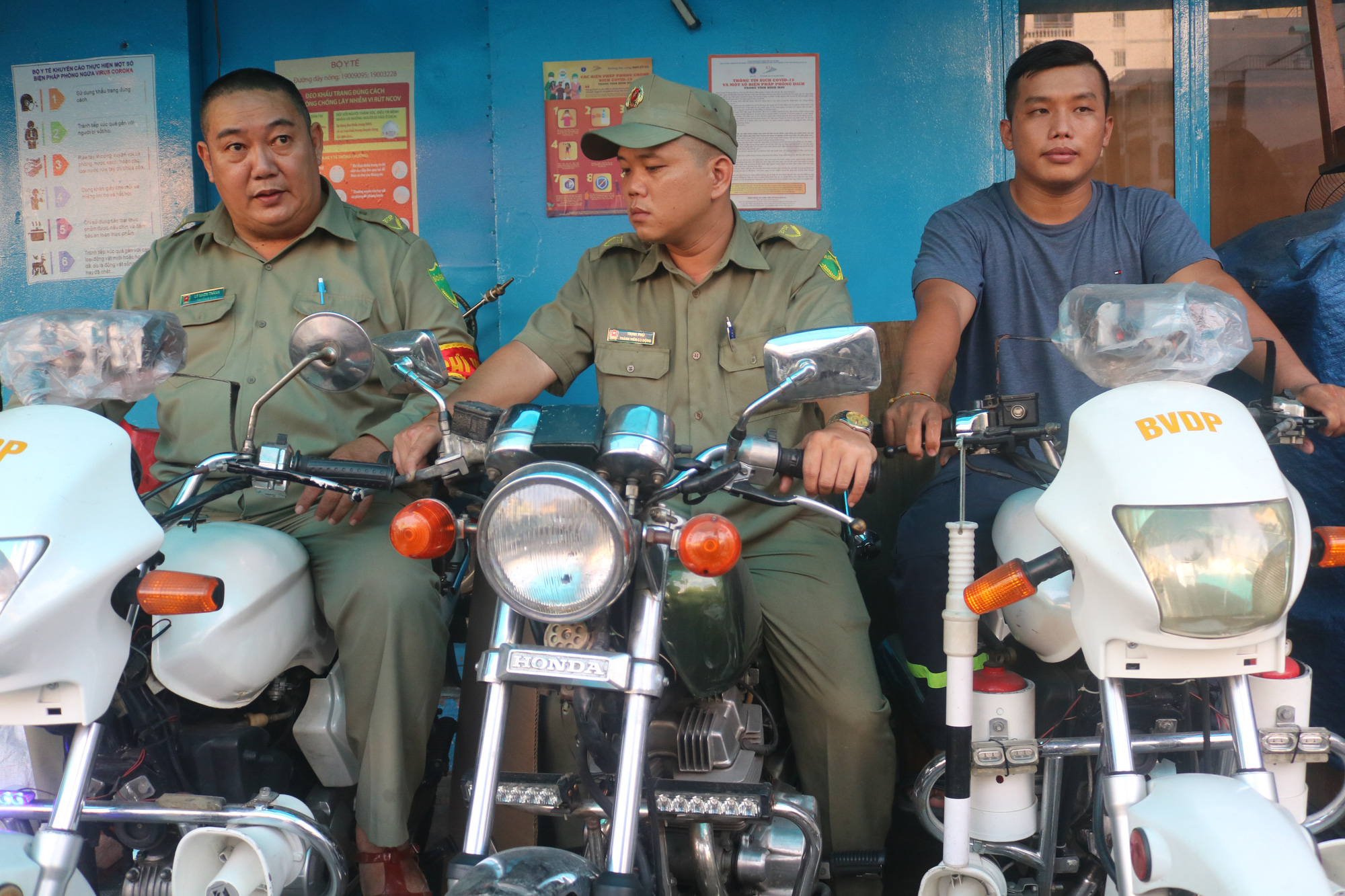 Ly Nhon Thanh (left) sits on his motorcycle next to two coworkers. He bought the motorcycle with his own money to chase robbers. Photo: Thu Hien / Tuoi Tre