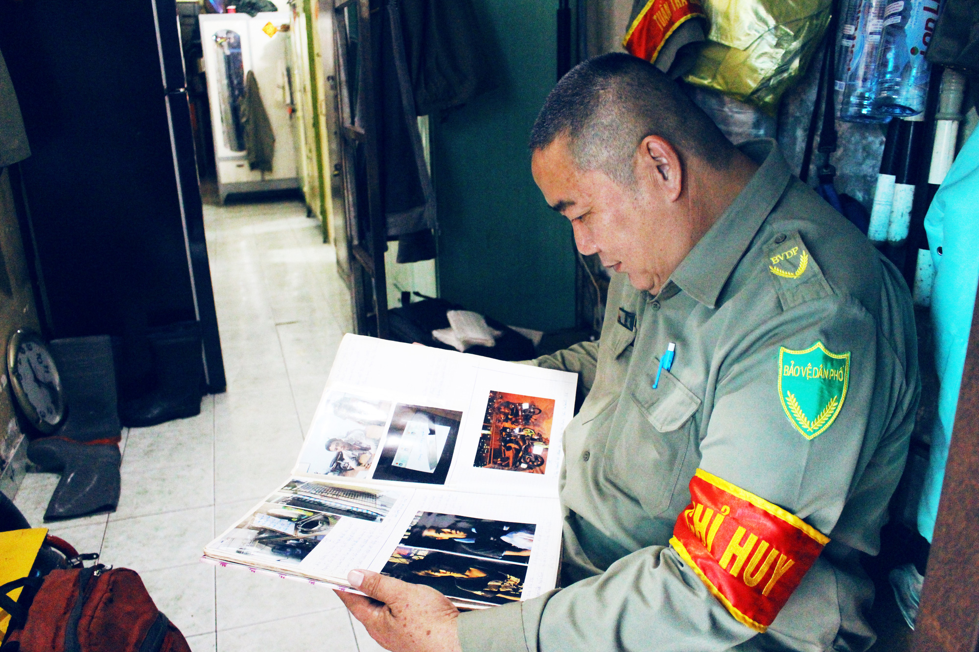 Ly Nhon Thanh looks at a journal where he keeps photos of his past cases of chasing after robbers. Photo: Kim Ut / Tuoi Tre