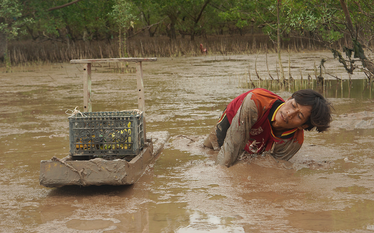 Tran Co, an experienced mud fisherman along Mo O Beach in Soc Trang Province in Vietnam's Mekong Delta, searches the mud for a catch. Photo: Minh Tam / Tuoi Tre