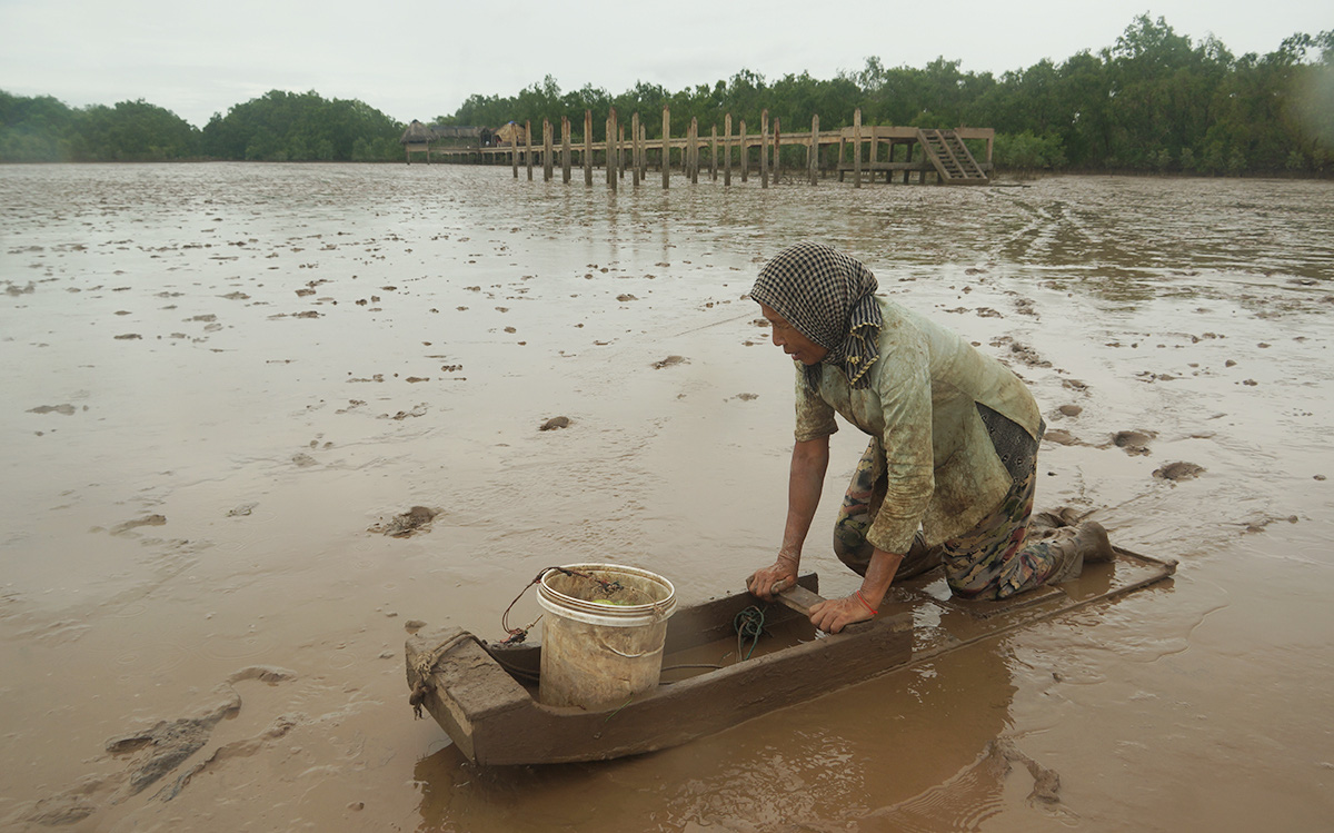 Binh, a 66-year-old woman with poor eyesight, works each day on the mud to make ends meet along Mo O Beach in Soc Trang Province in Vietnam's Mekong Delta. Photo: Minh Tam / Tuoi Tre