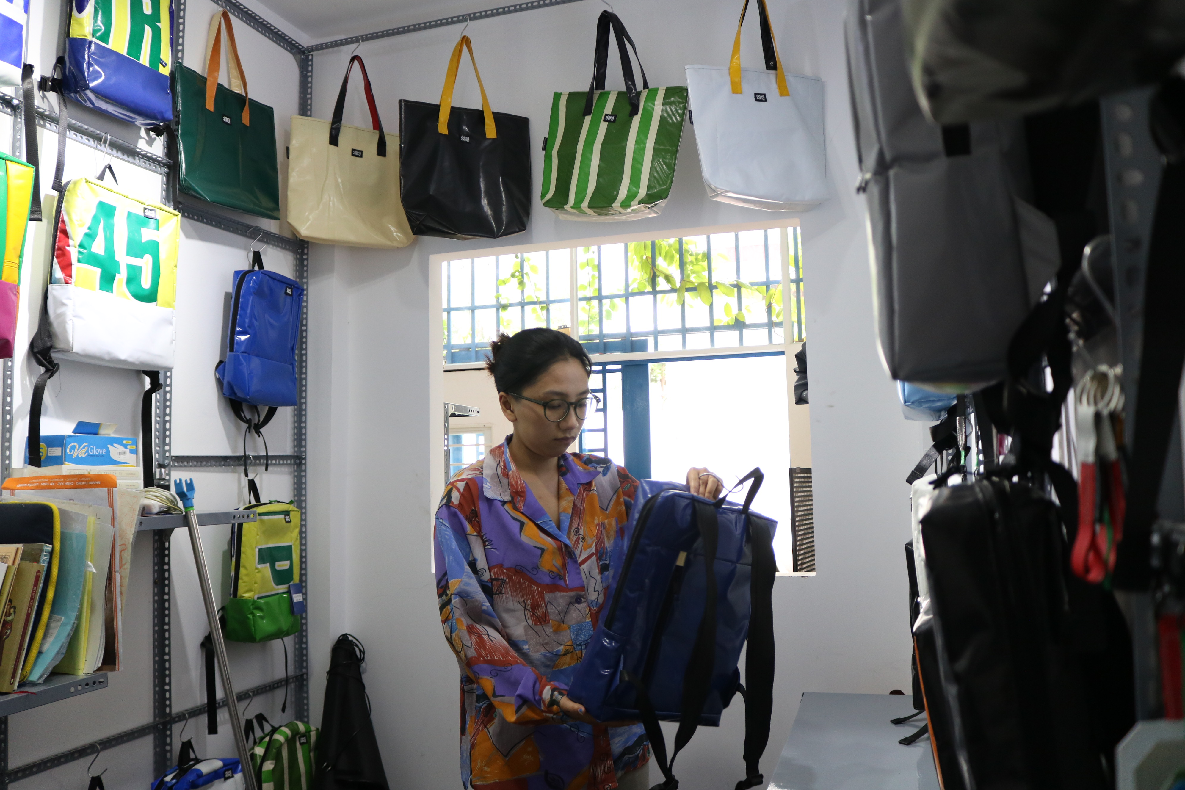 Thao Trang, co-founder of Dong Dong Sai Gon, arranges bags at a display area at the brand's workshop in Ho Chi Minh City, August 2020. Photo: Hoang An / Tuoi Tre