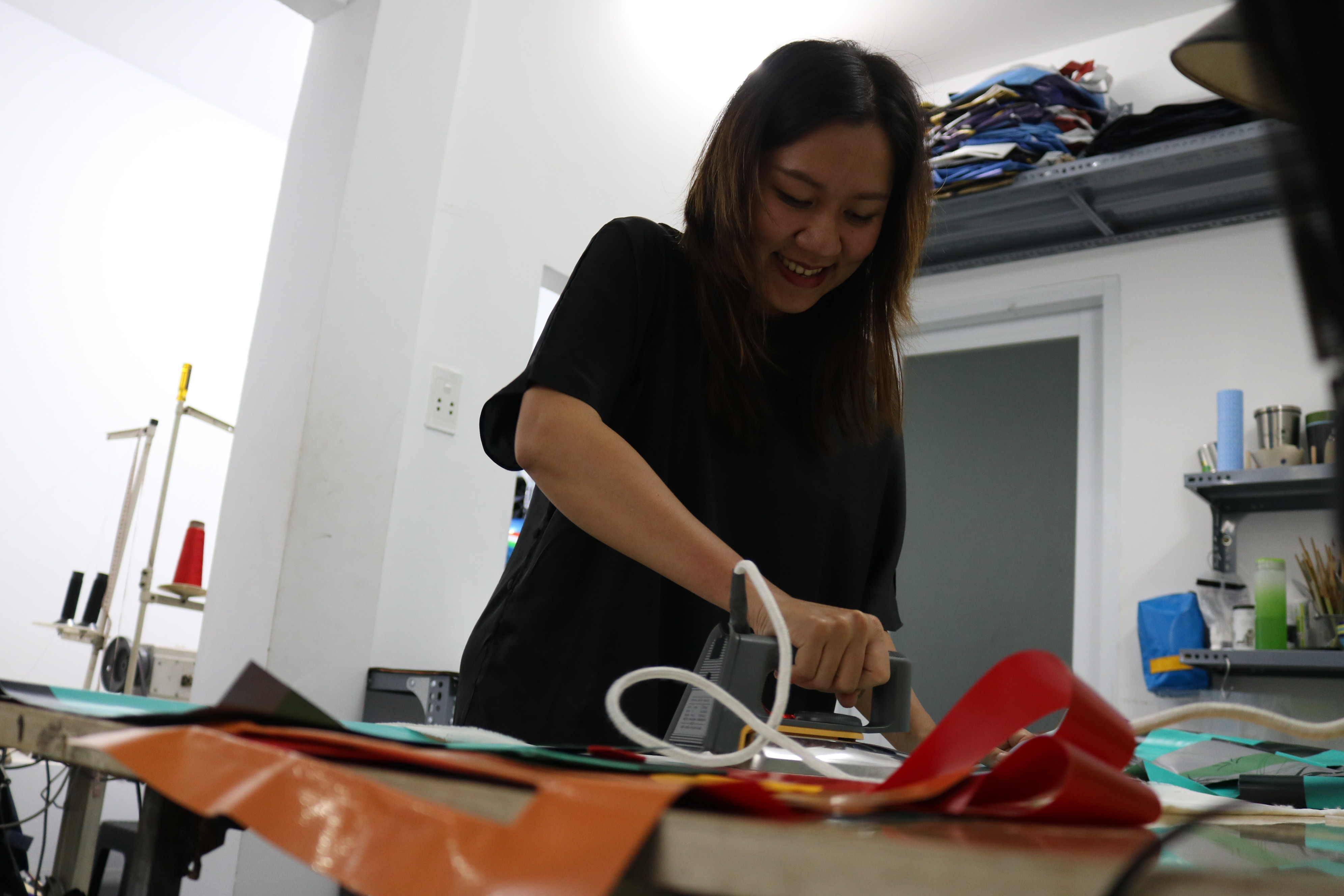 Kieu Anh, co-founder of Dong Dong Sai Gon, irons tarps before moving them to the next step for sewing at the brand's workshop in Ho Chi Minh City, August 2020. Photo: Hoang An / Tuoi Tre