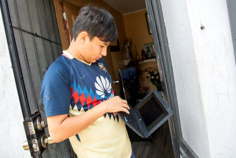 Angel, 13, stands outside his home trying to connect his computer to the wifi hotspot provided by a parked van from JFK company in order to follow his online classes in Santa Ana, California. Photo: AFP