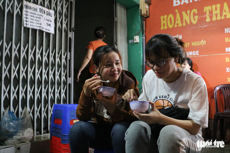 Nguyen Thi Kieu My (right), 24, has become a regular customer of Sau's 'chè' (a Vietnamese sweet dessert) stall for the past three years. Photo: Ngoc Phuong / Tuoi Tre