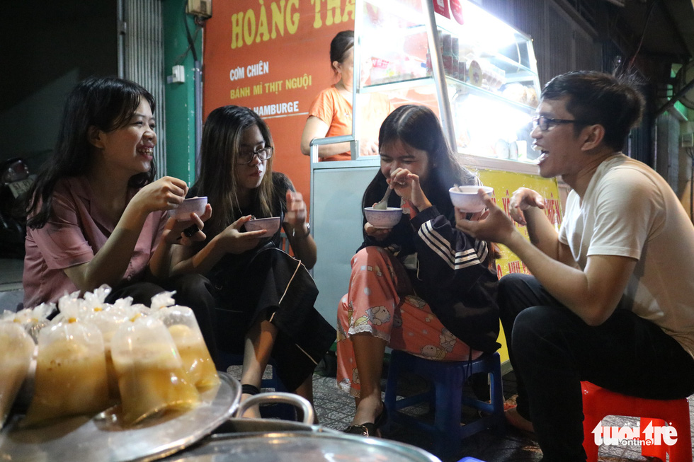 A group of regular customers chat as they enjoy 'chè' (a Vietnamese sweet dessert) at Sau's stall in Phu Nhuan District, Ho Chi Minh City. They said they love the open space while the oil lamp brings a feeling of nostalgia. Photo: Ngoc Phuong/ Tuoi Tre