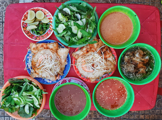 Two servings of Phan Rang-style 'banh xeo' (Vietnamese pancake) is served with four different types of condiments and a variety of raw veggies at an eatery in Ninh Thuan Province, Vietnam. Photo: Nhu Nguyen / Tuoi Tre