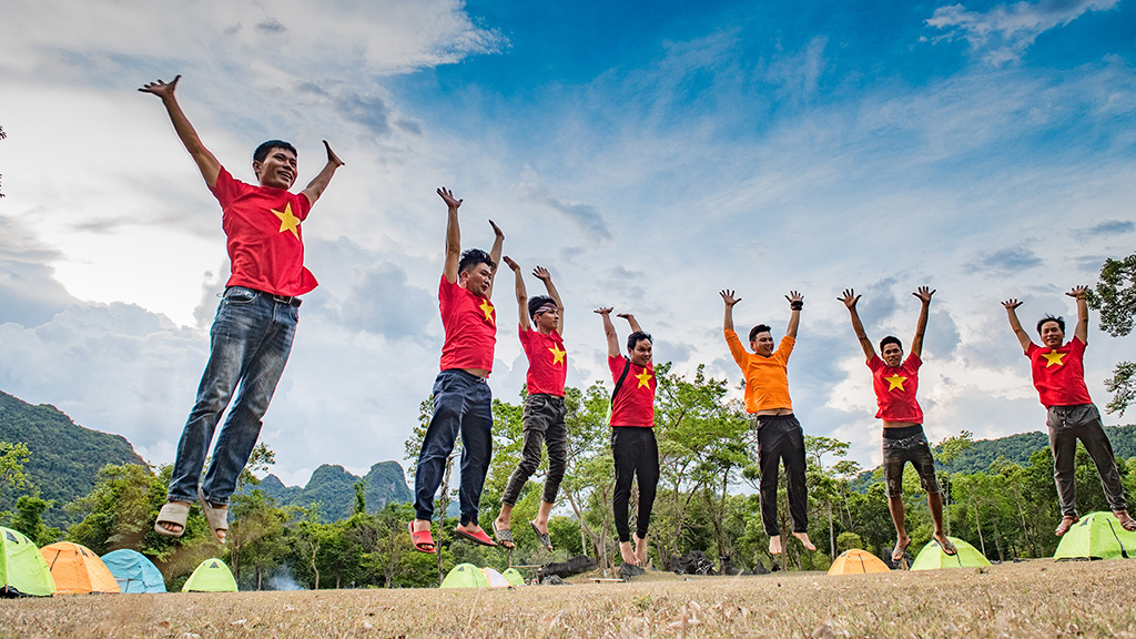 Visitors jump for a photo at a camp site after their expedition into the caves of Quang Binh Province, Vietnam. Photo: N.V.H.