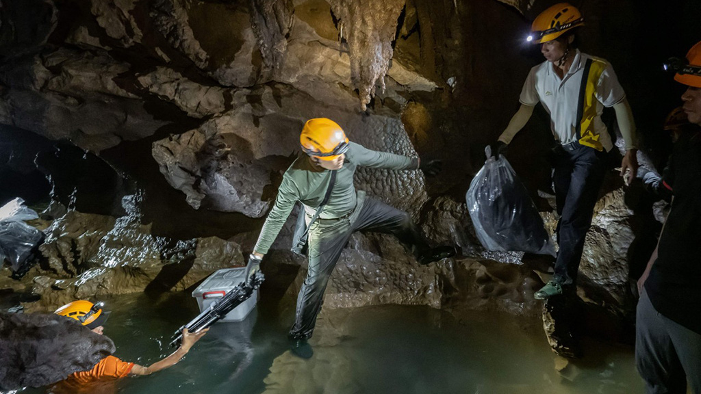 Expedition members pass photography and lighting devices through a stream inside a cave in Quang Binh Province, Vietnam. Photo: Hoang Nhiem