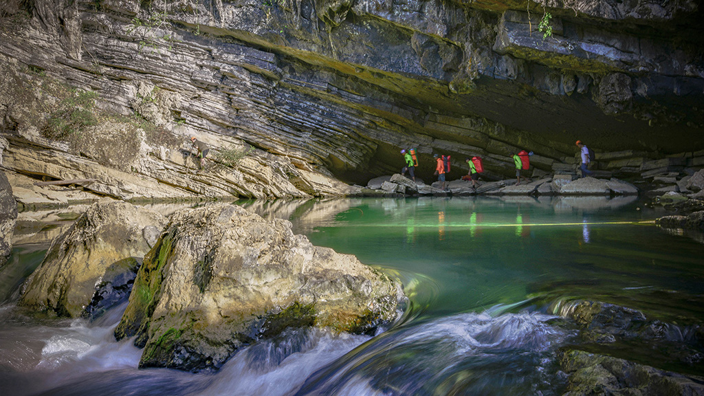 An expedition team walks past an emerald-colored pond before entering Tien Cave in Quang Binh Province, Vietnam. Photo: N.V.H.