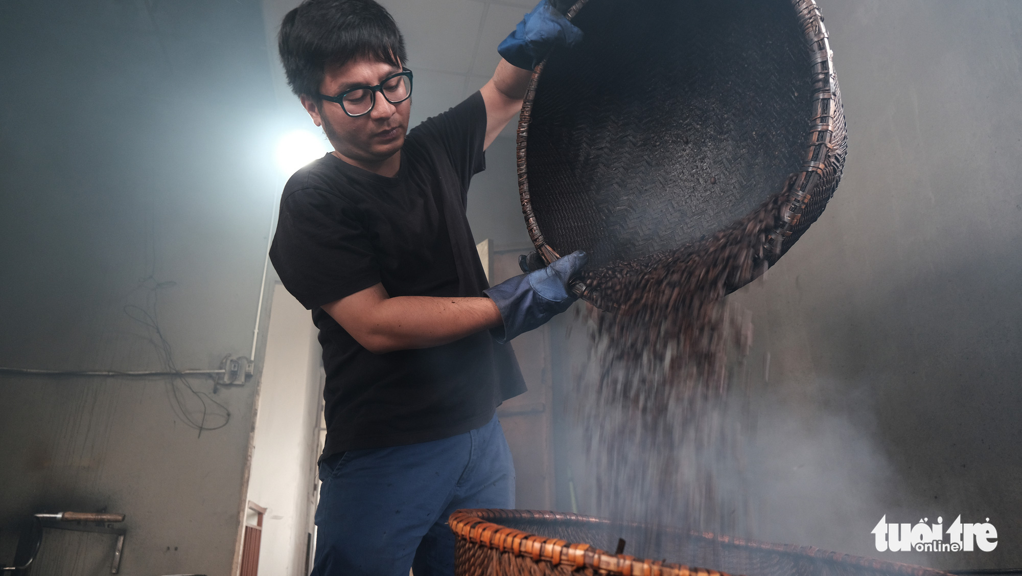 Nguyen Duc Hieu, the fourth-generation owner of Thai Café, hand-roasts coffee beans in the kitchen of his coffee shop on Trieu Viet Vuong Street in Hai Ba Trung District, Hanoi. Photo: Ha Thanh / Tuoi Tre
