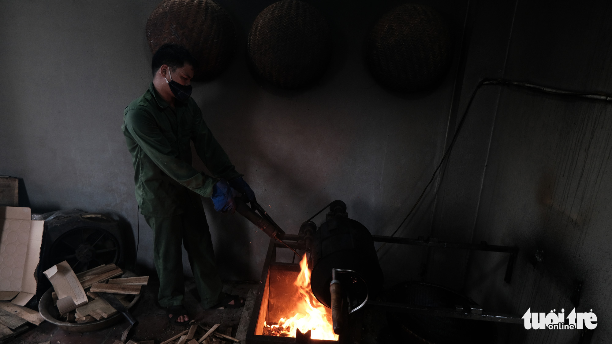 An employee hand-roasts coffee beans on a wood-fired stove in the kitchen of Thai Café on Trieu Viet Vuong Street in Hai Ba Trung District, Hanoi. Photo: Ha Thanh / Tuoi Tre