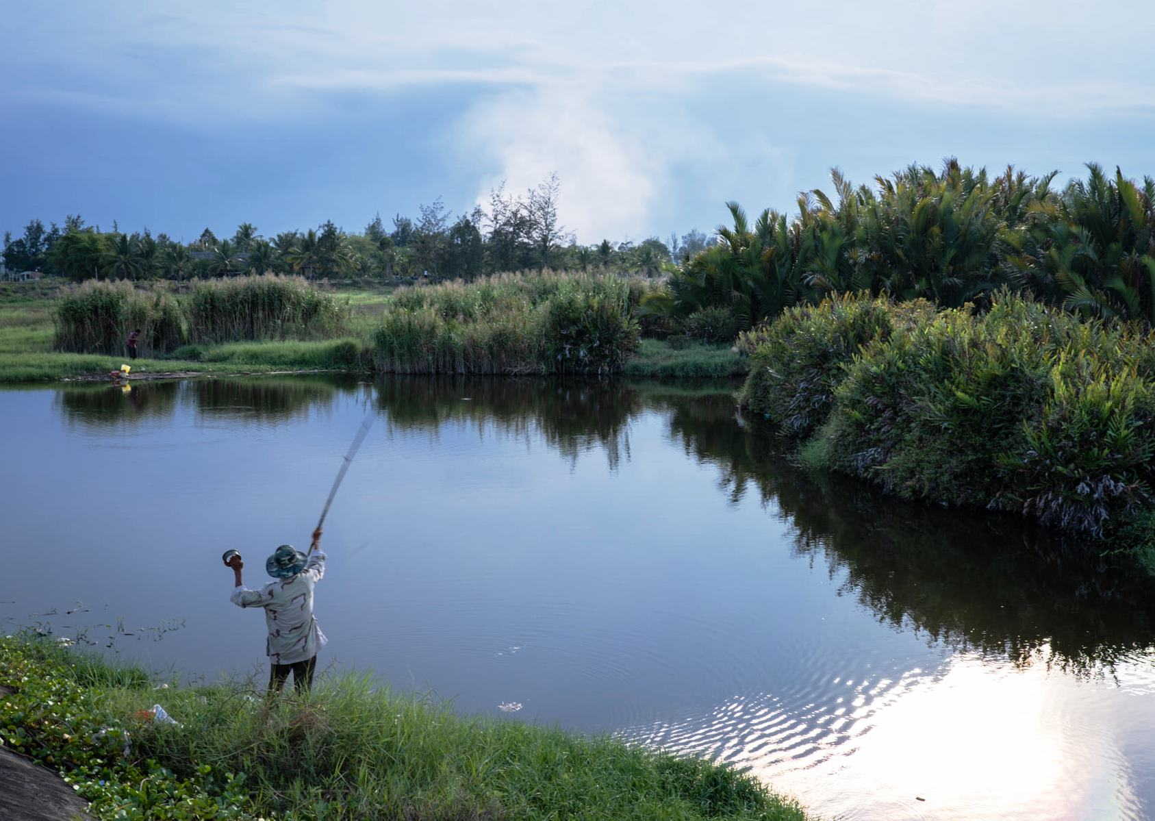 A man fishes at a river with smoke from the Cam Ha landfill in the background in Hoi An City, Quang Nam Province, Vietnam in this photo taken on September 10, 2020. Photo: Etienne Bossot